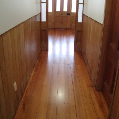 Lovely warm hallway with wood floor and panelling
