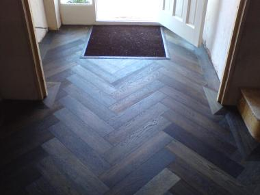 Mat well inlaid in a herringbone floor